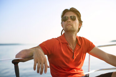 Man wearing sunglasses looking away while sitting on yacht against clear sky - CAVF03934