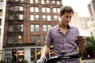 Low angle view of man with bicycle using mobile phone in city - CAVF03997