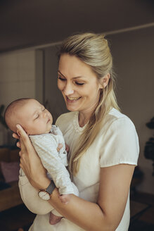 Smiling mother holding sleepy newborn baby - MFF04390