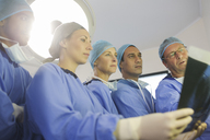 Surgeons looking at x-ray during surgery in operating theater - CAIF08435