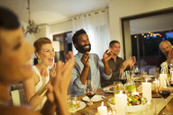 Friends cheering at dinner party - CAIF08468