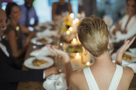Woman clapping at dinner party - CAIF08483