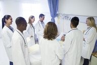 Doctor and residents examining patient in hospital room - CAIF08522
