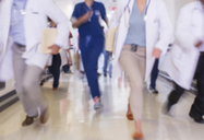 Doctors rushing in hospital hallway - CAIF08528