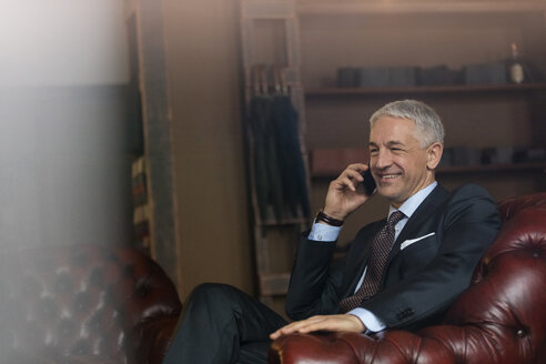 Smiling businessman talking on cell phone in menswear shop - CAIF08567