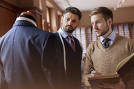 Tailors discussing suit and taking notes in menswear shop - CAIF08582