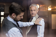 Tailor fitting businessman for suit in menswear shop - CAIF08600