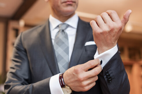 Close up well-dressed businessman adjusting cufflinks - CAIF08615