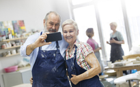 Senior couple taking selfie in pottery studio - CAIF08624