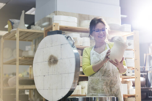 Smiling mature woman placing pottery vase in kiln in studio - CAIF08675