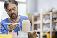 Focused mature man painting pottery vase in studio - CAIF08699