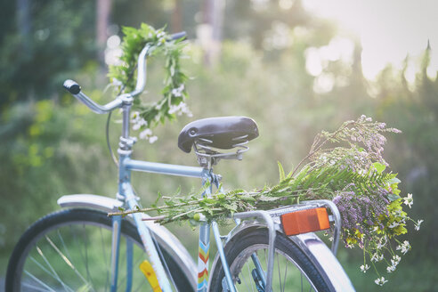 Flowers and garland on bicycle in garden - CAIF08714