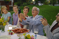 Senior man taking selfie with family at summer garden party dinner - CAIF08717