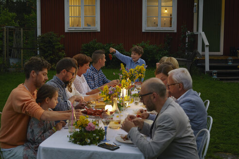 Family enjoying candlelight garden dinner party - CAIF08720