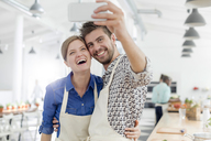 Enthusiastic couple taking selfie with camera phone in cooking class kitchen - CAIF08726