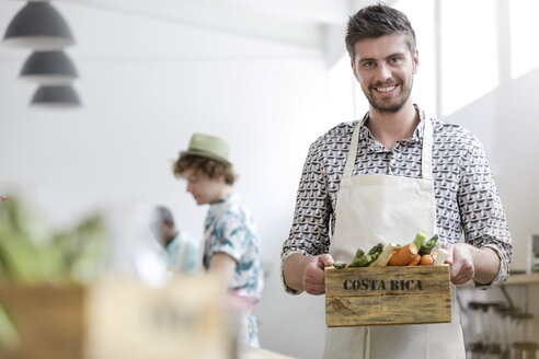 Portrait smiling man holding fresh vegetables in cooking class kitchen - CAIF08762