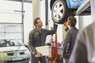 Mechanics examining and discussing tire in auto repair shop - CAIF08792