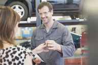 Mechanic taking keys from woman in auto repair shop - CAIF08810