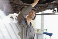 Mechanic working under car in auto repair shop - CAIF08825