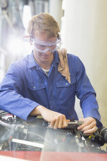 Mechanic working on engine in auto repair shop - CAIF08837