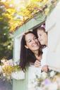 Smiling mother and daughter in playhouse window - CAIF08840