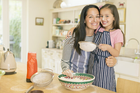 Portrait playful mother and daughter baking in kitchen with flour on faces - CAIF08864