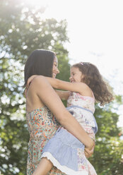 Affectionate mother holding and hugging daughter outdoors - CAIF08876