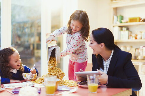 Girl pouring abundance of cereal at breakfast table - CAIF08879