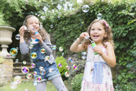 Carefree girls blowing bubbles in backyard - CAIF08882
