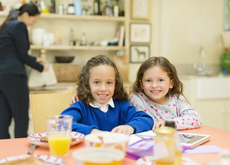 Portrait smiling sisters at breakfast table - CAIF08888