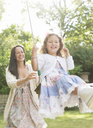 Mother in dress pushing daughter on swing in backyard - CAIF08891