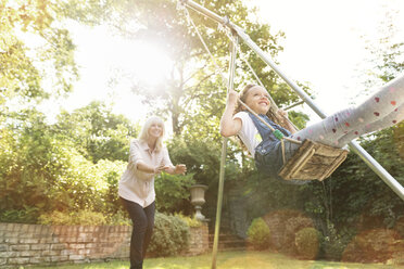 Grandmother pushing granddaughter on swing in backyard - CAIF08894
