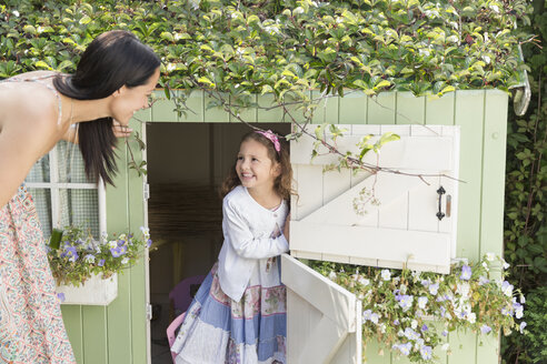 Mother and daughter at playhouse in garden - CAIF08897