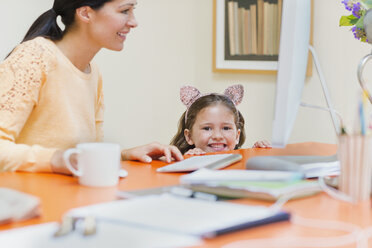 Portrait smiling girl in mouse ears headband with mother at computer - CAIF08900