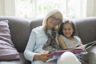 Grandmother and granddaughter reading book on living room sofa - CAIF08903