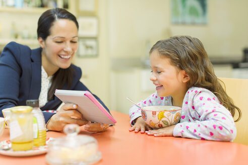 Mother and daughter using digital tablet at breakfast table - CAIF08906