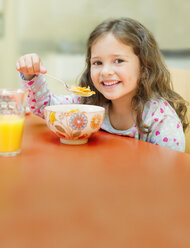 Portrait smiling girl eating cereal at breakfast table - CAIF08909