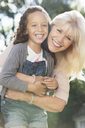 Portrait smiling grandmother and granddaughter hugging - CAIF08915
