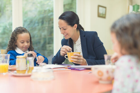 Working mother and daughter doing homework at breakfast table - CAIF08918