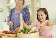 Grandmother and granddaughter preparing salad in kitchen - CAIF08921