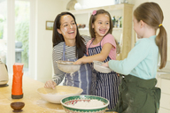 Laughing mother and daughters baking with flour on faces in kitchen - CAIF08924