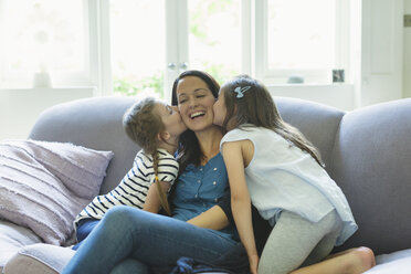 Daughters kissing mother's cheeks on living room sofa - CAIF08927