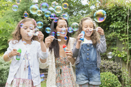 Mother and daughters blowing bubbles in backyard - CAIF08930