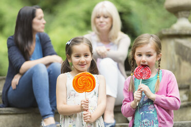 Girls with lollipops in park - CAIF08933