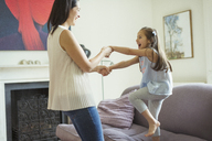 Playful mother and daughter dancing in living room - CAIF08939