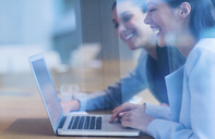 Laughing businesswomen working at laptop - CAIF08945