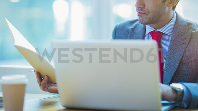 Focused businessman reviewing paperwork at laptop in office - CAIF08966
