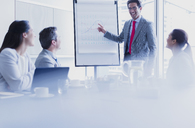 Smiling businessman leading meeting at flip chart in conference room - CAIF08972
