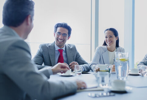 Smiling business people talking in conference room - CAIF08978