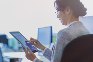 Businesswoman using digital tablet in office - CAIF08981